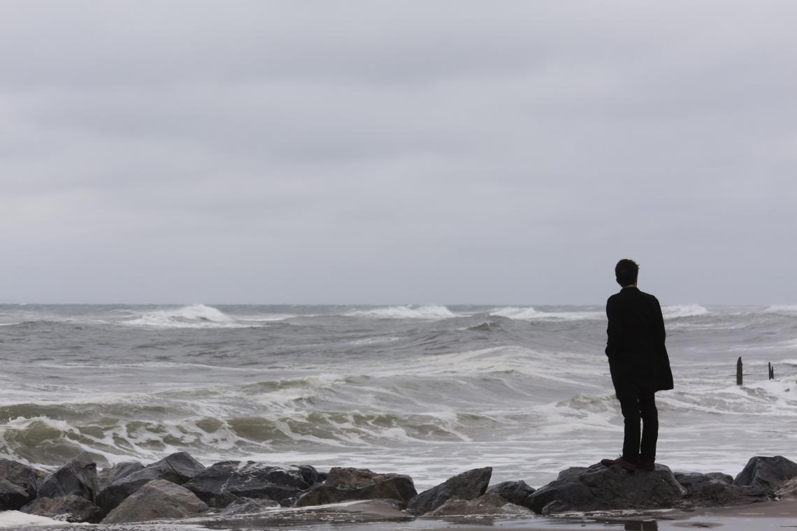 Man standing at edge of ocean